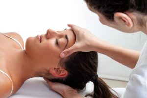 Close up of osteopath doing healing treatment on womans head. Hands doing massage on front and back of head.